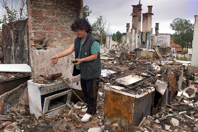 An Ethnic Albanian refugee from Kosovo looks at her destroyed kitchen after she returned to her house, 22 June 1999 on a road near Orahovac (AFP Photo)